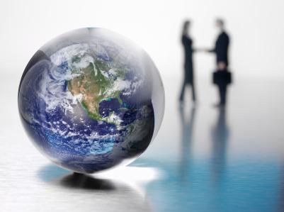 Im Vordergrund steht ein Globus, im Hintergrund eine Frau und ein Mann, beide an ihrer Kleidung als Geschäftsleute erkennbar. Sie schütteln sich die Hände.