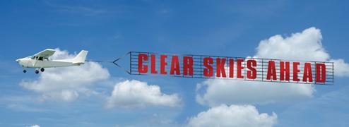 Das Bild zeigt einen blauen Himmel mit dicken weißen Wolken. Außerdem ein kleines Sportflugzeug, das ein Transparent mit der Aufschrift englischen Clear Skies Ahead zieht.