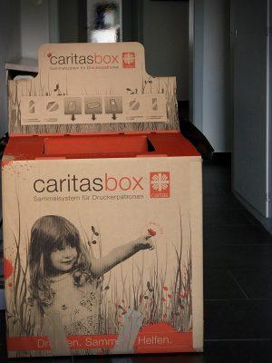 Nachhaltigkeit mit der CaritasBox. Das Sammelsystem für gebrauchte Druckerpatronen steht hier im Flur von TEXT_SITE Übersetzungen.