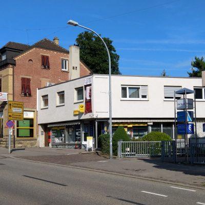 Im Vordergrund befindet sich eine Straße, rechts davon ein weißes Gebäude mit Flachdach. Unten eine Schaufensterfront mit dem Post-Logo.