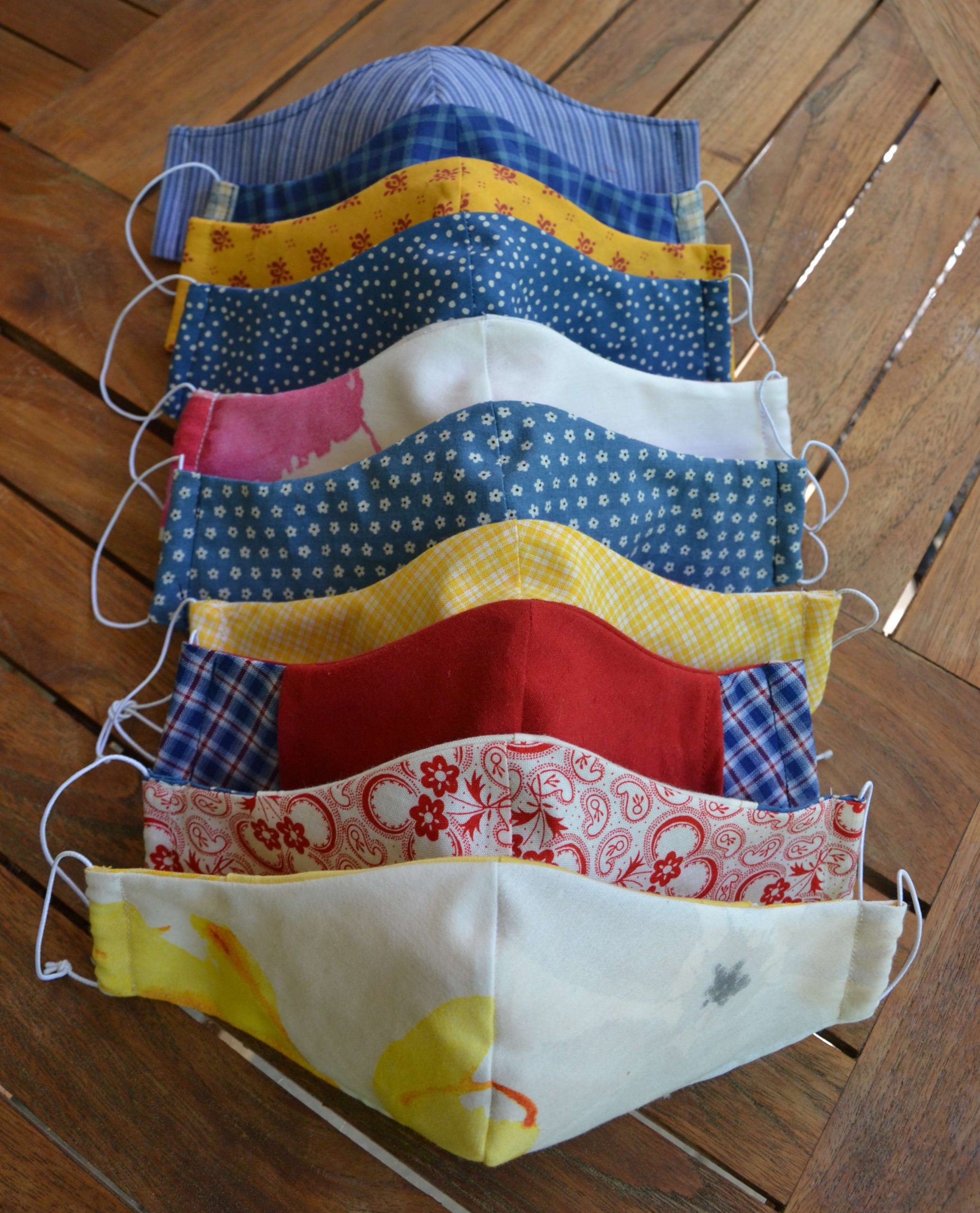Stapel von 9 Behelfsmasken in Gelb, Blau und Rot. Gemusterte und unifarbene Stoffe.
