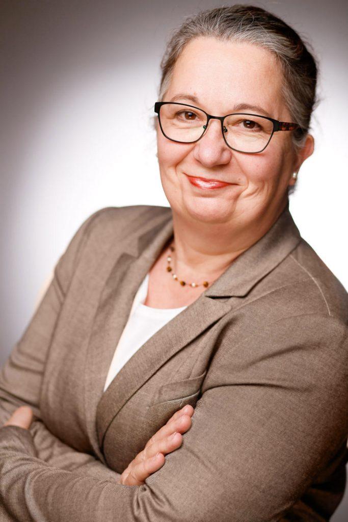 Das Profilbild von Birgit Bruder zeigt eine Frau mittleren Alters mit zurückgebundenen Haaren, Brille und beigefarbenem Blazer.